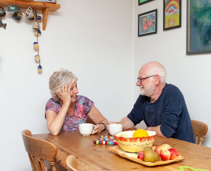 A happy couple sitting in the kitchen enjoying the warmth of their external wall insulation