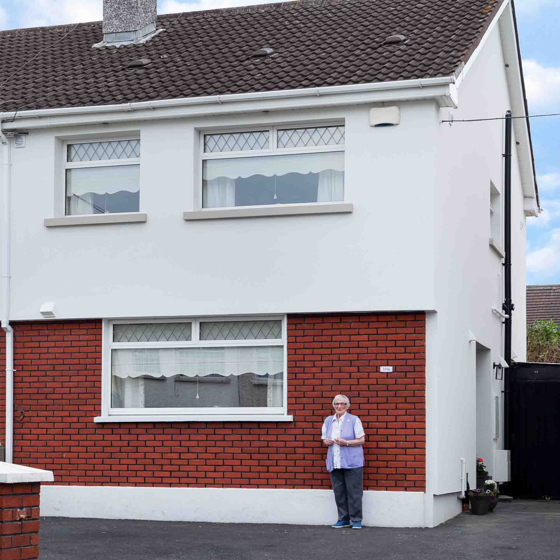 Elderly lady standing outside her home with external wall insulation