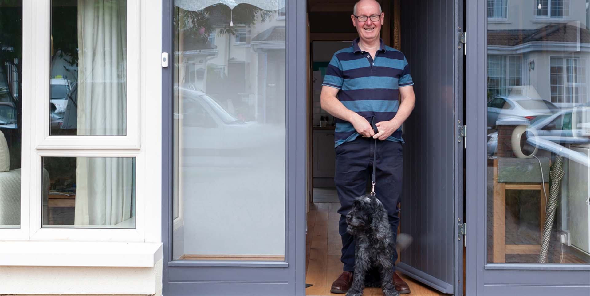 Man standing at the front of his Externally insulated house with his dog.