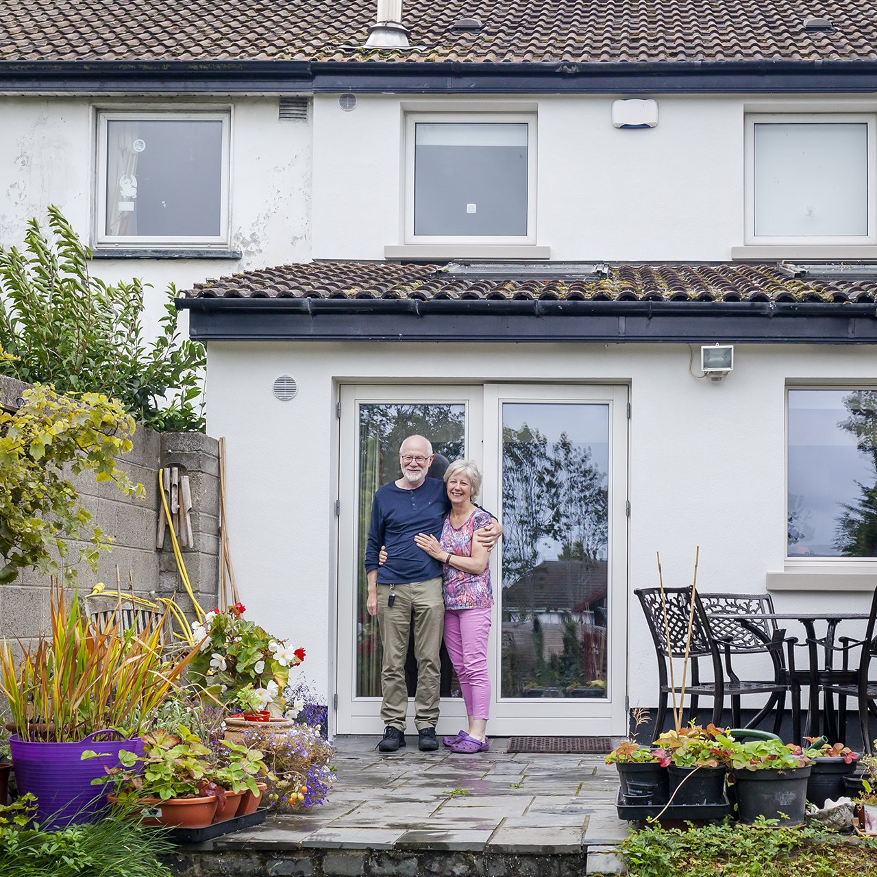 Happy couple standing outside thier house with External Wall Insulation