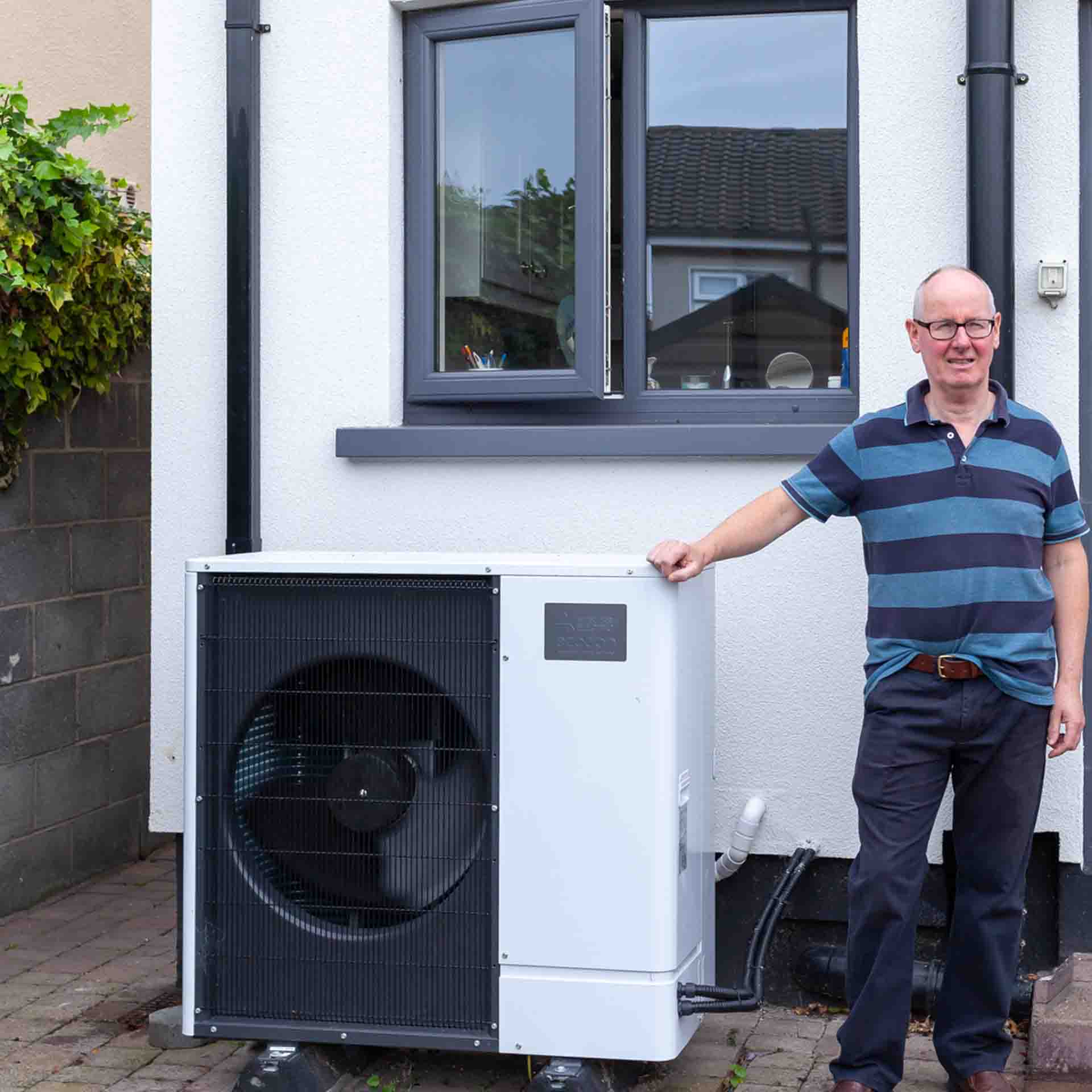 Man standing beside a Heat Pump outside his home