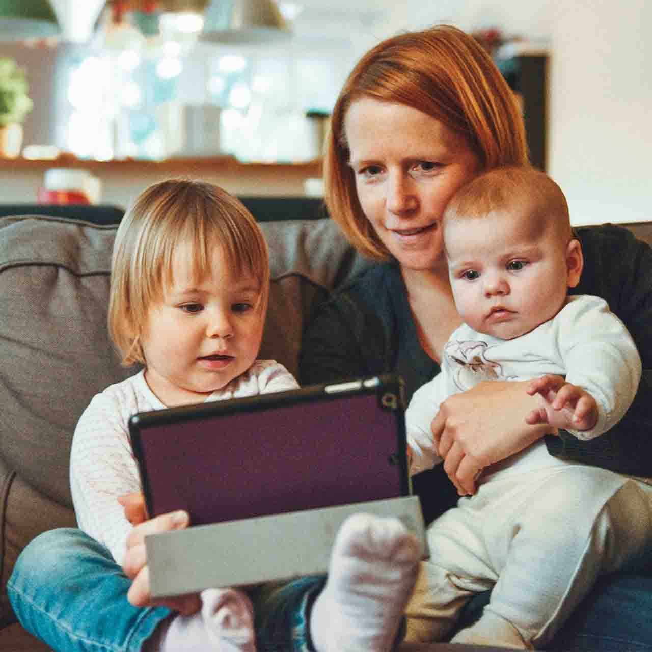 Young family in their living room looking at a tablet.